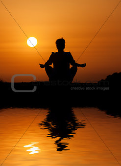 Silhouette woman sitting and relaxing against orange sunset