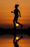 Silhouette woman running against orange sunset