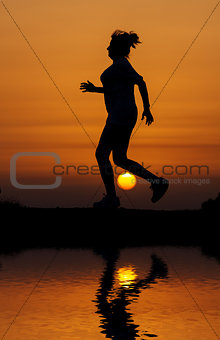 Silhouette woman running against orange sunset