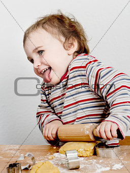 happy young child with rolling pin in grey background