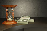 Hourglass and money on the desk.