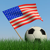 Soccer ball in the grass and the flag of USA