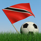 Soccer ball in the grass and the flag of Trinidad and Tobago