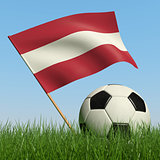 Soccer ball in the grass and flag of Latvia.
