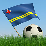 Soccer ball in the grass and the flag of Aruba