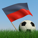 Soccer ball in the grass and the flag of Haiti