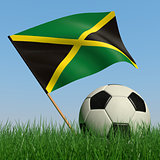 Soccer ball in the grass and the flag of Jamaica