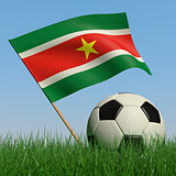 Soccer ball in the grass and the flag of Surinam