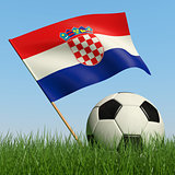 Soccer ball in the grass and flag of Croatia.