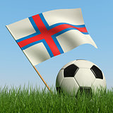 Soccer ball in the grass and flag of Faroe Islands.