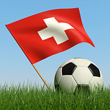 Soccer ball in the grass and flag of Switzerland.
