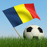 Soccer ball in the grass and flag of Romania.