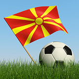 Soccer ball in the grass and flag of Macedonia.