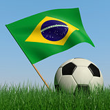 Soccer ball in the grass and the flag of Brazil