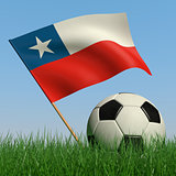 Soccer ball in the grass and the flag of Chile