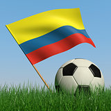 Soccer ball in the grass and the flag of Colombia