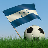 Soccer ball in the grass and the flag of Honduras
