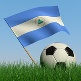 Soccer ball in the grass and the flag of Nicaragua
