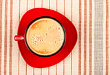 red coffee cup on striped tablecloth