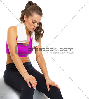 Tired young woman sitting on fitness ball
