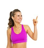 Smiling healthy young woman pointing on copy space