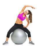 Happy fitness young woman making exercise on fitness ball