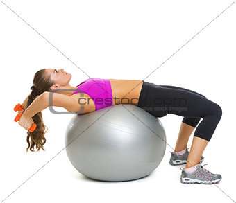 Fitness young woman making exercise with dumbbells on fitness ba