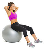 Healthy young woman making exercise on fitness ball