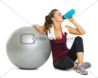 Fitness young woman with fitness ball drinking water