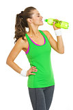 Happy fitness young woman drinking water