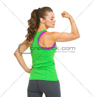 Portrait of female athlete showing biceps