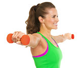 Closeup on dumbbell in hand of fitness young woman