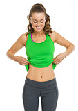 Happy fitness young woman showing belly