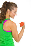 Happy female athlete making exercise with dumbbells