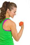 Happy female athlete making exercise with dumbbells