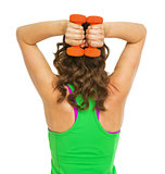 Fitness young woman making exercise with dumbbells . rear view