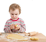 young child with rolling pin and dough