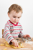 child working with dough on wooden desk