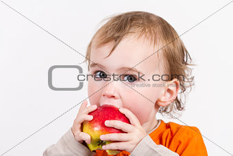 young child eating red apple