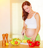 Pregnant woman cooking salad