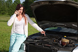 Young woman at a broken down car