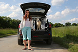 Young woman and a dog at a car