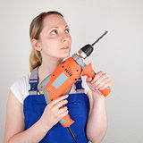 Young woman with drilling machine in her hands