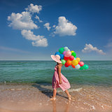Young woman walking on the beach with colored balloons / Relax