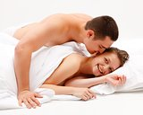 Man leaning over smiling woman in bed