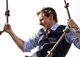 Strong, able businessman climbing ropes