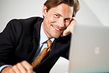 Smiling Caucasian businessman using laptop