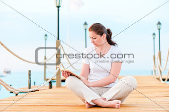 Young girl reading a book while sitting