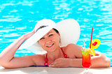 girl in a white hat relaxes in the pool