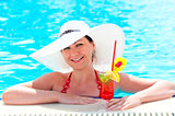 woman in the pool with a cocktail in a white hat